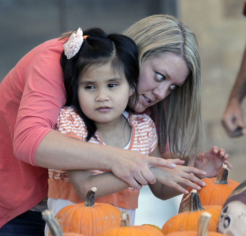 Al Hartmann  |  The Salt Lake Tribune Paraeducator Nikki Conk guides the hands of Elli Green who is totaly blind to feel the texture of pumpkins at Kauri Sue Hamilton School in Riverton Tuesday October 22.  More than 3,000 pumpkins grown by Utah prison inmates were given to the children.
