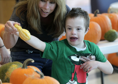 Al Hartmann  |  The Salt Lake Tribune Paraeducator Laurie Truckfield shows Thomas Soper a gourd among the pumpkins at Kauri Sue Hamilton School in Riverton Tuesday October 22.  More than 3,000 pumpkins grown by Utah prison inmates were given to  children.