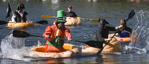 Keith Johnson  |  The Salt Lake Tribune Kyle Fox, left, and Jordan Rogers race to the finish line during the first heat of the Pumpkin Regatta at Sugar House Park in Salt Lake City on Saturday. Participants raced pumpkins weighing between 500 and 1,000 pounds.