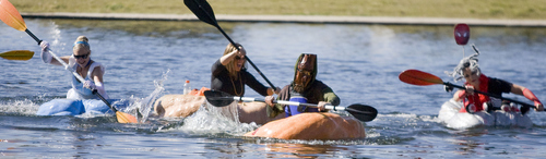 Keith Johnson  |  The Salt Lake Tribune Cheryl Shelley, left, Carrie Fox, Dan Farr and Aubrey Kruisman compete in one of the heats during the Pumpkin Regatta at Sugar House Park in Salt Lake City, October 19, 2013. Participants raced pumpkins weighing between 500 and 1,000 pounds.