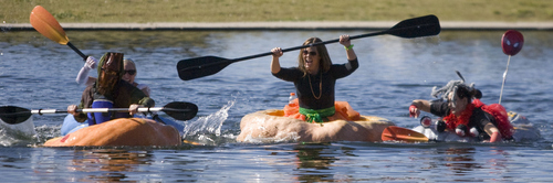 Keith Johnson  |  The Salt Lake Tribune Carrie Fox, center, battles with Dan Farr, left, and Aubrey Kruisman during a heat of the Pumpkin Regatta at Sugar House Park in Salt Lake City, October 19, 2013. Participants raced pumpkins weighing between 500 and 1,000 pounds.