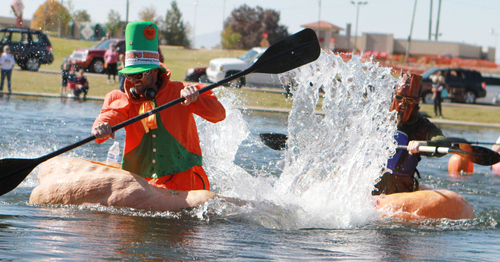Keith Johnson  |  The Salt Lake Tribune Kyle Fox, left, paddles past Dan Farr during the Pumpkin Regatta at Sugar House Park in Salt Lake City, October 19, 2013. Participants raced pumpkins weighing between 500 and 1,000 pounds.