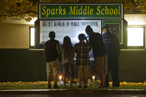 Children and a parents take a photo of a memorial with candles at Sparks Middle School on Monday, Oct. 21, 2013 in Sparks, Nev. The 12-year-old student who opened fire on the middle school campus, wounding two classmates and killing a teacher before he turned the gun on himself, got the weapon from his home, authorities said Tuesday. School District police said they are still working to determine how the boy obtained the 9mm semi-automatic Ruger handgun used in the Monday morning spree at Sparks Middle School. The boy's parents are cooperating with authorities and could face charges in the case, police said.  (AP Photo/The Sacramento Bee, Hector Amezcua)  MAGS OUT; LOCAL TV OUT (KCRA3, KXTV10, KOVR13, KUVS19, KMAZ31, KTXL40); MANDATORY CREDIT
