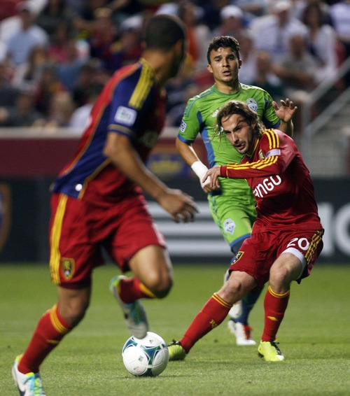 Kim Raff  |  The Salt Lake Tribune (right) Real Salt Lake midfielder Ned Grabavoy (20) passes the ball to (left) Real Salt Lake forward Alvaro Saborio (15) as (back) Seattle Sounders FC midfielder Servando Carrasco (23) looks on during the second half at Rio Tinto Stadium in Sandy on June 22, 2013. Real went on to win the game 2-0.