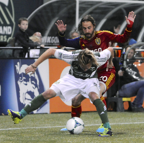 Portland Timbers' Michael Harrington works for the ball in front of Real Salt Lake's Ned Grabavoy during the first half of an MLS soccer game in Portland, Ore., Saturday, Oct. 19, 2013. (AP Photo/Greg Wahl-Stephens)