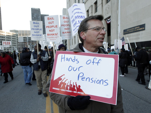 Dennis Marton walks with protesters at a rally outside The Theodore Levin United States Courthouse in Detroit, Wednesday, Oct. 23, 2013. An unusual trial starts Wednesday, pitting Detroit's emergency manager and his legal team against unions and pension funds that claim the city isn't qualified to scrub its books clean under Chapter 9 bankruptcy. (AP Photo/Paul Sancya)