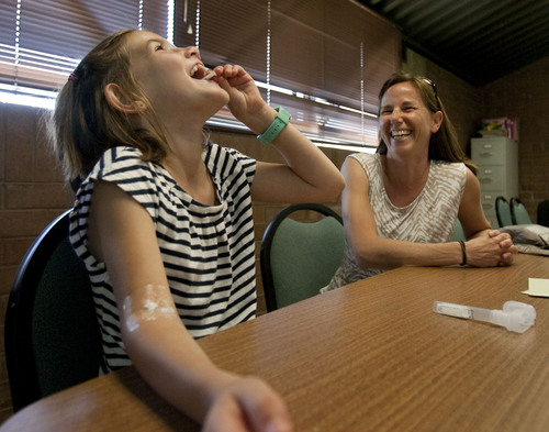 Steve Griffin | The Salt Lake Tribune Cindy Solomon laughs as her eight-year-old daughter, Ella Solomon, eats a bag of sugar in order to produce saliva that will be tested during her visit to the Huntsman Cancer Institute. The institute is part of the Legacy study, an effort to tease out environmental, genetic, dietary and other factors in the development of breast cancer.