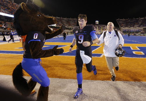 Boise State quarterback Grant Hedrick (9) is greeted by the Broncos' mascot after Boise State defeated Nevada 34-17 in an NCAA college football game, Saturday, Oct. 19, 2013 in Boise, Idaho. Hedrick stepped in after starting quarterback Joe Southwick left the game with an injury in the first quarter. (AP Photo/Ted S. Warren)