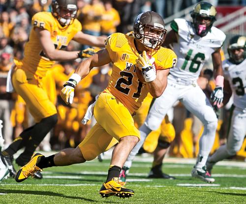 Wyoming's Shaun Wick (21) runs the ball during an NCAA college football game against Colorado State on Saturday, Oct. 19, 2013, in Laramie, Wyo. (AP Photo/Laramie Boomerang, Jeremy Martin)