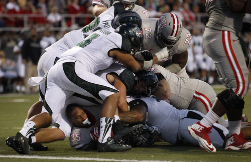 UNLV running back Tim Cornett lies at the bottom of a pile without his helmet after he was tackled by Hawaii players during an NCAA college football game in Las Vegas, Saturday, Oct. 12, 2013. (AP Photo/Las Vegas Review-Journal, John Locher)  LOCAL TV OUT; LOCAL INTERNET OUT; LAS VEGAS SUN OUT