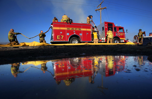 Francisco Kjolseth  |  The Salt Lake Tribune Salt Lake City Fire engine 7 crews pack up the hoses following a two-alarm blaze Wednesday morning on a rural lot along the west Salt Lake City and Magna city line .