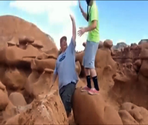 This frame grab from a video taken by Dave Hall shows  two men cheering after a Boy Scouts leader knocked over an ancient Utah desert rock formation at Goblin Valley State Park. Authorities are mulling whether to press charges against the scout leader and against the two men who cheered him on after they posted video of the incident online. (AP Photo/Dave Hall)