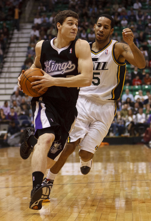 Trent Nelson  |  The Salt Lake Tribune Sacramento's Jimmer Fredette drives on Utah Jazz guard Devin Harris (5) in the second half of game Saturday at the EnergySolutions Arena in Salt Lake City. The Jazz downed the Kings, 96-93.