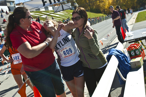 Chris Detrick  |  The Salt Lake Tribune Skyline senior Jeni Townsend is helped after competing in the 4A state cross country race at Sugar House Park Wednesday October 23, 2013. Ogden senior Sarah Feeny won with a time of 17:25.0.