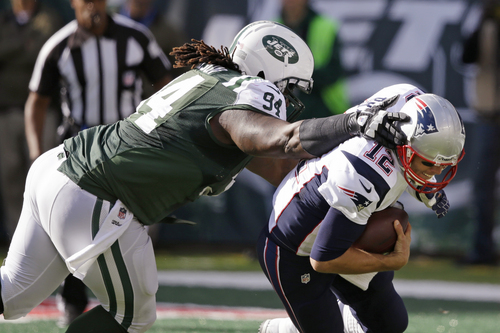 New York Jets nose tackle Damon Harrison (94) sacks New England Patriots' Tom Brady (12) during the second half of an NFL football game Sunday, Oct. 20, 2013, in East Rutherford, N.J.  (AP Photo/Seth Wenig)