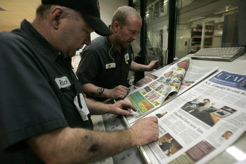 Pressmen Rich Wallin, left, and Bill Wall look over the quality of the printing of The Salt Lake Tribune at the controls of the TKS press Wednesday, March 11, 2009 at MediaOne in West Valley City. MediaOne prints many papers and products including The New York Times, USA Today, The Deseret News, Provo Daily Herald and The Salt Lake Tribune. Jim Urquhart/The Salt Lake Tribune; 3/11/09
