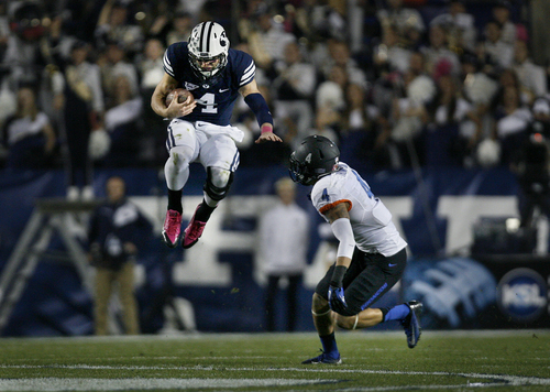 Scott Sommerdorf   |  The Salt Lake Tribune BYU QB Taysom Hill inexplicably jumps near the end of a scramble as he was about to be tackled by Boise State Broncos safety Darian Thompson (4). BYU held a 24-3 lead over Boise State at the half, Friday, October 25, 2013.