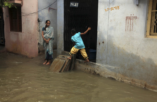 An Indian child balances herself on dry area as she crosses a flooded street in Hyderabad, India, Friday, Oct. 25, 2013. Heavy rains triggered by northeast monsoon have lashed several parts of Andhra Pradesh state for the fourth consecutive day Friday prompting authorities to evacuate many residents from low-lying areas, according to local reports. (AP Photo/Mahesh Kumar A.)