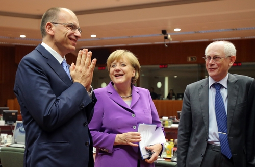 Italian Prime Minister Enrico Letta, left, gestures while speaking with German Chancellor Angela Merkel, center, and European Council President Herman Van Rompuy during a round table meeting at an EU summit on Friday, Oct. 25, 2013. Migration, as well as an upcoming Eastern Partnership summit, will top the agenda in Friday's meeting of EU leaders. (AP Photo/Michel Euler)