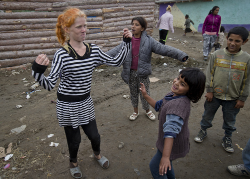 """Minka Ruseva, daughter of Sasha Ruseva, left, dances along with other children in a Roma neighborhood of Nikolaevo, Bulgaria, Friday, Oct. 25, 2013. Sasha Ruseva, a Bulgarian Roma woman from this town, is under investigation by Bulgarian authorities trying to find out  if she is the mother of a suspected abduction victim in neighboring Greece known as """"Maria"""" whose case has triggered a global search for her real parents. (AP Photo/Vadim Ghirda)"""