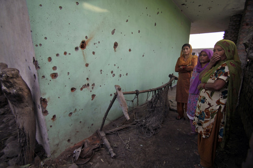 Indian women look at shell marks allegedly caused from firing from Pakistan side at Garkhal village near the India-Pakistan international border, 35 kilometers (22 miles) from Jammu, India, Friday, Oct. 25, 2013. An Indian official says at least 10 civilians have been wounded as Pakistani troops fired guns and mortar shells at more than a dozen Indian border posts overnight in the disputed Himalayan region of Kashmir. (AP Photo/Channi Anand)