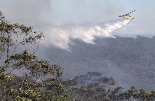 A helicopter drops water on bush land in Faulcombridge, 85 kilometers (53 miles) west of Sydney, Australia, Thursday, Oct. 24, 2013. More than 100 wildfires have killed one resident and destroyed more than 200 homes in New South Wales state this month. (AP Photo/Rob Griffith)