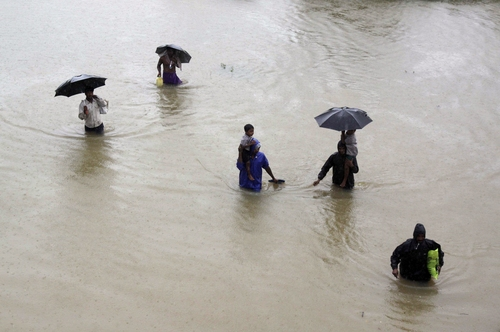 Villagers wade through floodwaters to reach safer areas in Khurda district, in the eastern Indian state of Orissa, Friday, Oct. 25, 2013. Low pressure induced rains has flooded several parts of the state leaving hundreds of thousands marooned even as choppers launched rescue operations Friday, according to news reports. The area was hit by a powerful cyclone two weeks ago. (AP Photo/Biswaranjan Rout)