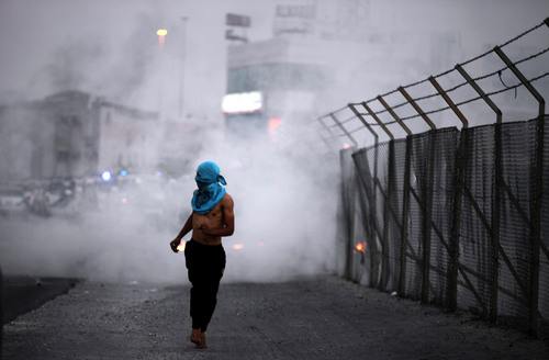 A Bahraini anti-government protester runs from tear gas fired by riot police during clashes in Qaddam village, Bahrain, just west of the capital of Manama, on Friday, Oct. 25, 2013. Clashes erupted after a few thousand people participated in a  march in nearby Karrana organized by opposition societies, calling for democracy and for the Gulf kingdom's long-serving prime minister to step down. (AP Photo/Hasan Jamali)