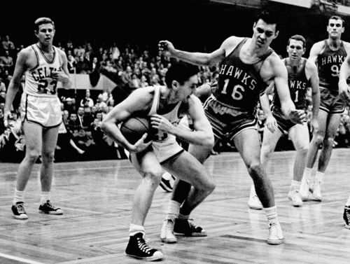 FILE - In this March 30, 1958, file photo, Boston Celtics'  Bill Sharman holds the ball as St. Louis Hawks' Cliff Hagan (16), defends, during the second half of an NBA Finals basketball game in Boston. Sharman, the Hall of Famer who won NBA titles as a player for the Boston Celtics and a coach for the Los Angeles Lakers, has died. He was 87.  Sharman died Friday, Oct. 25, 2013, at his home in Redondo Beach, the Lakers announced. (AP Photo/J. Walter Green, File)