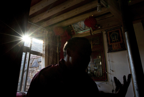 In this Wednesday, Oct. 16, 2013 photo, a Tibetan, cousin of Sangay Gyatso speaks during an interview, under a portrait of the Dalai Lama at a room in Gannan Tibetan Autonomous Prefecture, China. By the official account, Sangay Gyatso was an incorrigible thief and womanizer who was goaded into setting himself on fire in an elaborate and cruel scheme to fan up ethnic hatred. But one year after the 27-year-old father of two fatally set himself ablaze near a white stupa near his Gannan village, his cousin denied the government's account. (AP Photo/Andy Wong)