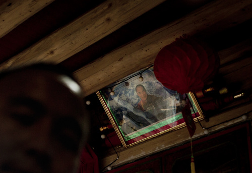 In this Wednesday, Oct. 16, 2013 photo, a Tibetan, cousin of Sangay Gyatso sits near a portrait of the Dalai Lama at a room in Gannan Tibetan Autonomous Prefecture, China. By the official account, Sangay Gyatso was an incorrigible thief and womanizer who was goaded into setting himself on fire in an elaborate and cruel scheme to fan up ethnic hatred. But one year after the 27-year-old father of two fatally set himself ablaze near a white stupa near his Gannan village, his cousin denied the government's account. (AP Photo/Andy Wong)