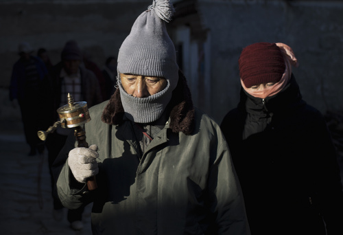 In this Thursday, Oct. 17, 2013 photo, Tibetan pilgrims offer prayers near the historic Labrang Monastery in Xiahe, Gansu Province, China.  By the official account, Sangay Gyatso who lit himself on fire and burned to death near a white stupa near his Gannan village, was an incorrigible thief and womanizer who was goaded into setting himself on fire in an elaborate and cruel scheme to fan up ethnic hatred. But one year after Sangay Gyatso's self-immolation, his cousin denied the government's account. Since early 2009, overseas Tibetan rights groups have reported that more than 120 Tibetans - monks and lay people, men and women, and young and elderly - have self-immolated in protest of China's suppressive rule of the Himalayan regions. (AP Photo/Andy Wong)