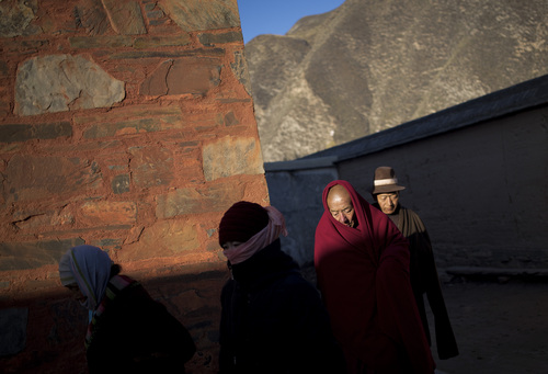 In this Thursday, Oct. 17, 2013 photo, a Tibetan monk and pilgrims circle a Buddhist temple to offer prayers near the historic Labrang Monastery in Xiahe, Gansu Province, China. By the official account, Sangay Gyatso who lit himself on fire and burned to death near a white stupa near his Gannan village, was an incorrigible thief and womanizer who was goaded into setting himself on fire in an elaborate and cruel scheme to fan up ethnic hatred. But one year after Sangay Gyatso's self-immolation, his cousin denied the government's account. Since early 2009, overseas Tibetan rights groups have reported that more than 120 Tibetans - monks and lay people, men and women, and young and elderly - have self-immolated in protest of China's suppressive rule of the Himalayan regions. (AP Photo/Andy Wong)