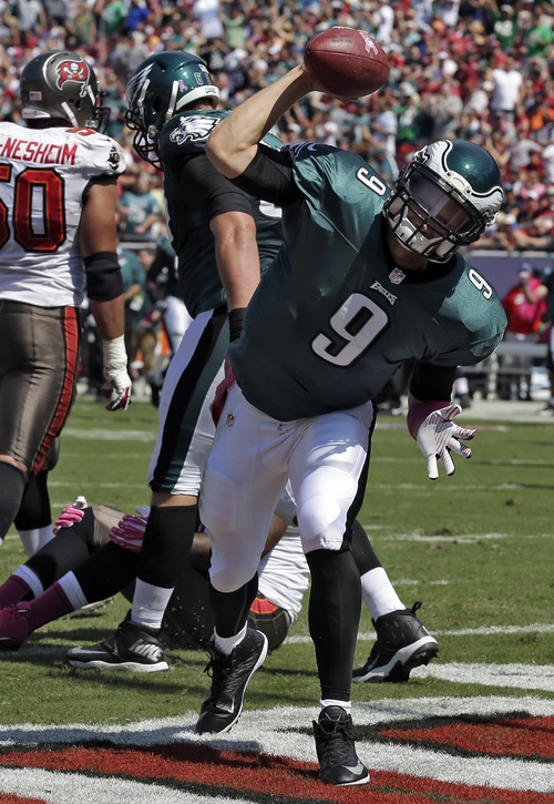 Philadelphia Eagles quarterback Nick Foles (9) spikes the football after scoring on a four-yard touchdown run during the first quarter of an NFL football game against the Tampa Bay Buccaneers Sunday, Oct. 13, 2013, in Tampa, Fla. (AP Photo/Chris O'Meara)