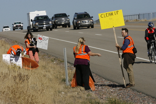 Scott Sommerdorf  |  The Salt Lake Tribune The group Restore the Fourth (amendment) works on its first cleanup on Redwood Road in front of the new NSA Data Center on Saturday. The group adopted the road, using the cleanup as a Rally Against Mass Surveillance. Amy and Shan Morris, Lorina Potter and Dan Garfield carry signs and clean up trash on Redwood Road.