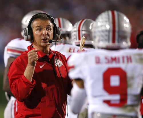 Ohio State head coach Urban Meyer talks to wide receiver Devin Smith (9) during the second half of an NCAA college football game against the Northwestern on Saturday, Oct. 5, 2013, in Evanston, Ill. Ohio State won 40-30. (AP Photo/Charles Rex Arbogast)