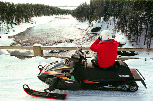 "A snowmobiler stops on a bridge just above the Grand Canyon of the Yellowstone River in Yellowstone National Park in Wyo., in February, 2000. A federal judge on Friday, Oct. 15, 2004,  struck down a ban on snowmobiles in Yellowstone and Grand Teton national parks, calling it a ""prejudged, political"" move. The decision could clear the way for new rules that allow the machines. (AP Photo/Billings Gazette)"