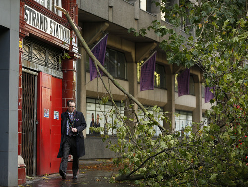 A man walks in a sidewalk partially blocked by trees outside Strand station in London, Monday Oct. 28, 2013. A major storm with hurricane-force winds is lashing southern Britain, causing flooding and travel delays including the cancellation of roughly 130 flights at London's Heathrow Airport. (AP Photo/PA, Jonathan Brady) UNITED KINGDOM OUT,  NO SALES,  NO ARCHIVES