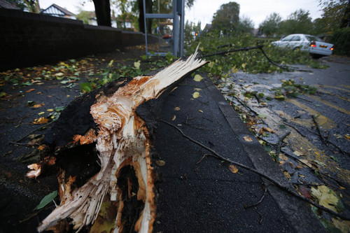 A fallen tree branch partially blocks a pavement and road in London, Monday, Oct. 28, 2013. A major storm with hurricane-force winds is lashing southern Britain, causing flooding and travel delays including the cancellation of roughly 130 flights at London's Heathrow Airport.Some rail lines shut down Monday morning, and some roads were closed due to fallen trees and power lines.Air travelers and commuters were advised to check conditions before starting any journeys. Widespread delays were expected as major London train lines delayed their opening because of the winds and tree hazards.(AP Photo/Lefteris Pitarakis)