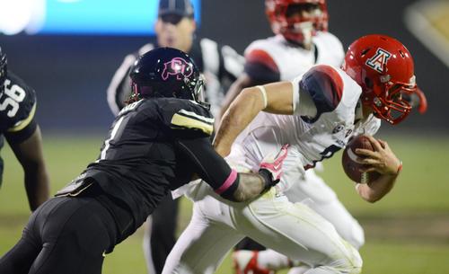 Derrick Webb of Colorado tackles Arizona quarterback, B.J. Denker,  during the Oct.26, 2013 game in Boulder, Colorado. (AP Photo/The Daily Camera, Cliff Grassmick)