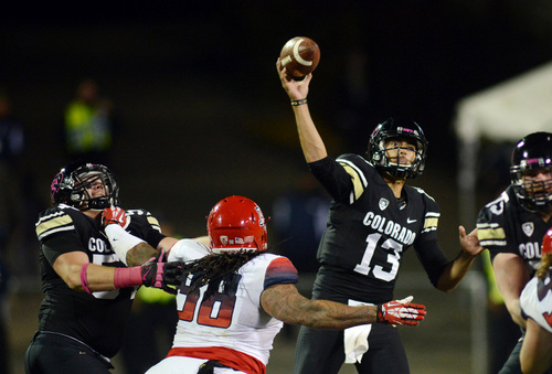 Colorado's Sefo Liufau (13) throws while being pressured by Arizona's Tevin Hood, center, during an NCAA college football game on Oct. 26, 2013, in Boulder, Colo. (AP Photo/The Daily Camera, Cliff Grassmick)