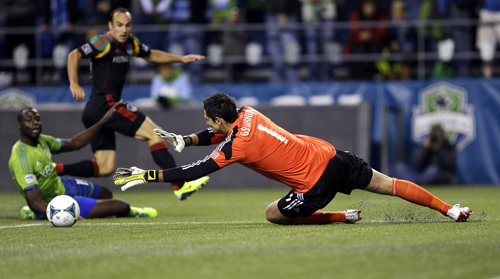 Seattle Sounders goalkeeper Michael Gspurning, right, dives for the ball as Los Angeles Galaxy's Landon Donovan, second from left, and Souners' Djimi Traore, left, watch in the first half of an MLS soccer match, Sunday, Oct. 27, 2013, in Seattle. (AP Photo/Ted S. Warren)
