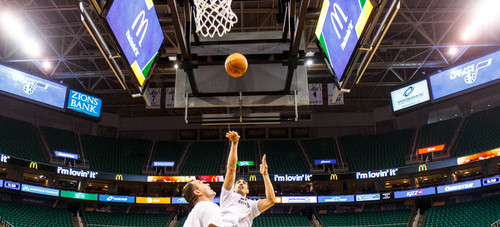 Trent Nelson  |  The Salt Lake Tribune Utah Jazz center Enes Kanter (0) shoots over assistant coach Alex Jensen during warmups as the Utah Jazz host the Oklahoma City Thunder, NBA Basketball at EnergySolutions Arena in Salt Lake City, Wednesday October 30, 2013.