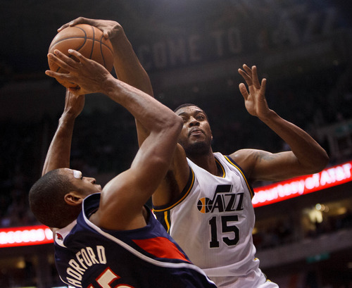 Trent Nelson  |  The Salt Lake Tribune Utah Jazz power forward Derrick Favors (15) gets his hand on a shot by Atlanta Hawks center Al Horford (15) as the Utah Jazz host the Atlanta Hawks, NBA basketball Wednesday, February 27, 2013 in Salt Lake City.