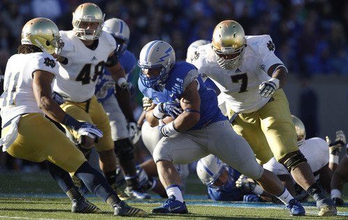 Air Force running back D.J Johnson, center, is surrounded by, from left to right, Notre Dame defenders Matthias Farley, Dan Fox and Stephon Tuitt while running for a short gain in the second quarter of an NCAA college football game in Air Force Academy, Colo., Saturday, Oct. 26, 2013. (AP Photo/David Zalubowski)