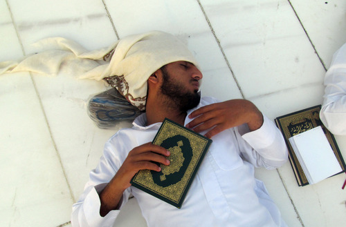 A Muslim pilgrim holds a copy of Islam's holy book Quran as he sleeps at the Grand Mosque in the Muslim holy city of Mecca, Saudi Arabia, Friday, Oct. 11, 2013. Every Muslim is required to perform the hajj, or pilgrimage, to Mecca at least once in his or her lifetime if able to do so. (AP Photo/Amr Nabil)