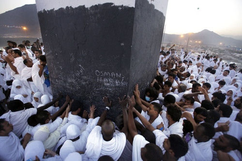 Muslim pilgrims touch a marker at the top of a rocky hill called the Mountain of Mercy, near the holy city of Mecca, Saudi Arabia, Monday, Oct. 14, 2013. The trek to the site is itself the answer to a lifetime of prayers for many Muslims. Hajj is a central pillar of Islam and the pilgrimage is one that all able-bodied Muslims are required to perform once in their lives.(AP Photo/Amr Nabil)