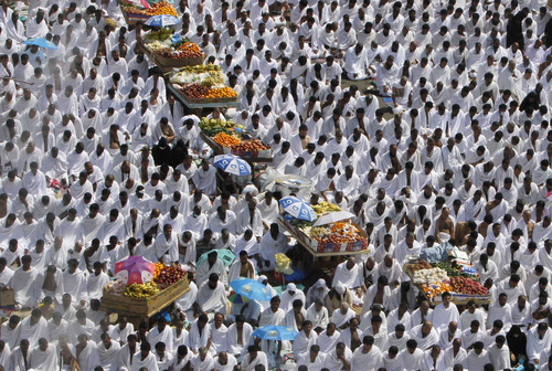 Muslim pilgrims pray the noon prayers near fruit carts in Arafat, near the holy city of Mecca, Saudi Arabia, Monday, Oct. 14, 2013. As part of the hajj, or pilgrimage, the faithful head to a hill called Jabal al-Rahmah, meaning Mountain of Mercy, about 20 kilometers (12 miles) east of Mecca, that Muslims believe the Prophet Muhammad called on people to abolish their feuds and put aside their racial, economic and tribal differences. (AP Photo/Amr Nabil)