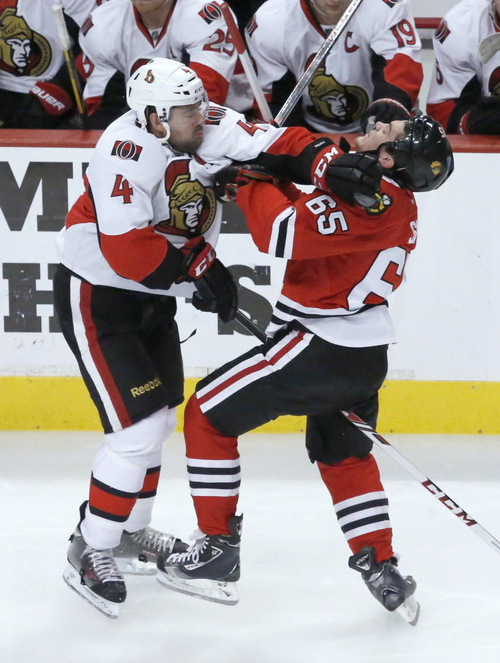 Ottawa Senators defenseman Chris Phillips (4) and Chicago Blackhawks center Andrew Shaw collide during the third period of an NHL hockey game Tuesday, Oct. 29, 2013, in Chicago. The Blackhawks won 6-5. (AP Photo/Charles Rex Arbogast)