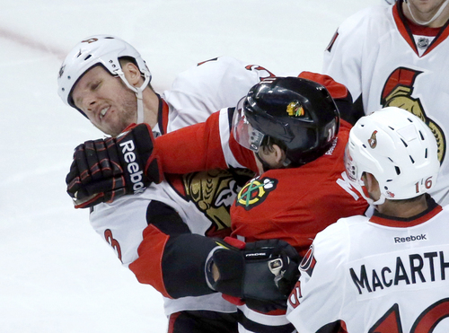 Chicago Blackhawks left wing Jeremy Morin, right, pushes on the face of Ottawa Senators defenseman Marc Methot (3) during the second period of an NHL hockey game Tuesday, Oct. 29, 2013, in Chicago. (AP Photo/Charles Rex Arbogast)